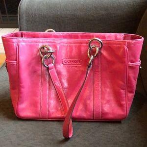 pink Coach on shoulder or in hand larger bag.